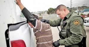 Un agente de la Patrulla Fronteriza de EU arresta a un inmigrante ilegal al cruzar de México a EU. por San Ysidro..