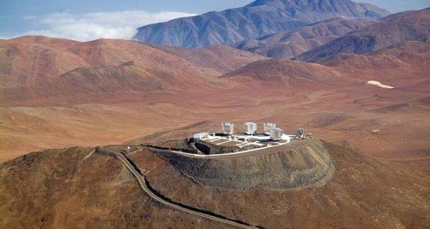 A spectacular aerial view of the ESO Very Large Telescope (VLT) platform, atop Cerro Paranal, in the Chilean Atacama Desert. The VLT consists of an array of four giant 8.2-metre Unit Telescopes (UTs), that can observe together or individually, and four 1.8-metre Auxiliary Telescopes (ATs) dedicated to interferometry. UTs and ATs are visible in the picture. On the right side of the platform is the 2.6-metre VLT Survey Telescope (VST), while on the left edge the Control Building, where astronomers operate the telescopes during the night, is partially visible. The Paranal Observatory is located at 2600 metres altitude, in the Taltal district, some 120 km south of Antofagasta, in the II Region of Chile. In the background, at the upper edge of the image, is the Pacific Ocean, only 12 km west from the observatory and typically covered by clouds. This is due to the fact that the cold oceanic stream keeps the thermal inversion layer very low, guaranteeing exceptional conditions for ground-based astronomy.